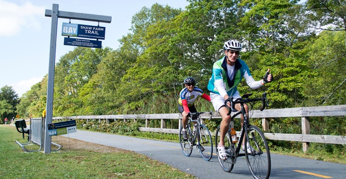 two cyclists ride down bike path in Fairhaven