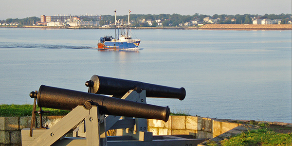 a fishing vessel steams past the cannons at Fort Phoenix State Reservation