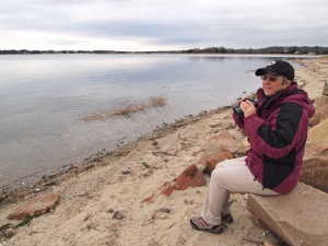 woman holding binoculars sitting on beach at Nasketucket Bay State Reservation