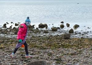 a girl walks on the beach in Wareham in winter